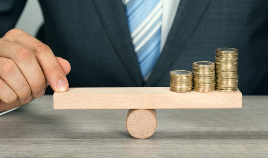 Bild Geschäftsmann balanciert Münzen auf Holzwaage